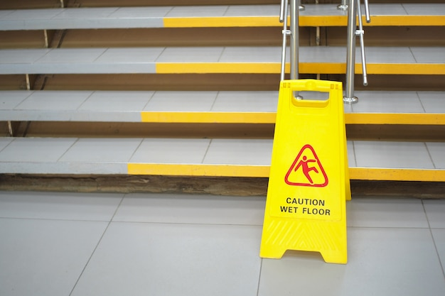 Waarschuwingsbord met russische tekst let op natte vloer. een bord bij de trap in het winkelcentrum