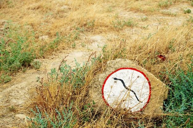 Waarschuwingsbord op een steen in de buurt van het pad.