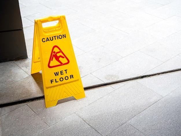 Waarschuwingsbord voor natte vloeren op een loopbrug in de buurt van het gebouw na regen
