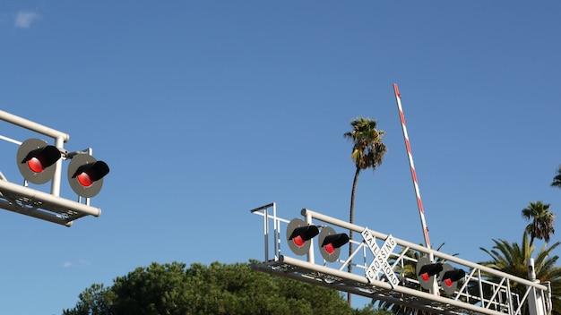 Waarschuwingssignaal spoorwegovergang in de vs. crossbuck-bericht en rood verkeerslicht op de kruising van spoorwegen in californië.