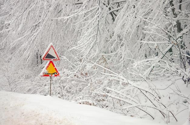 Waarschuwingsverkeersteken op de sneeuw berijpte takken