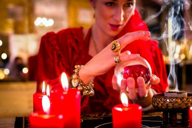 Waarzegger in seance met kristallen bol en rook
