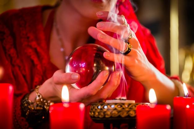 Waarzegger of esoterisch orakel, ziet in de toekomst door in hun kristallen bol te kijken, wierook te branden en kaarsen te verlichten