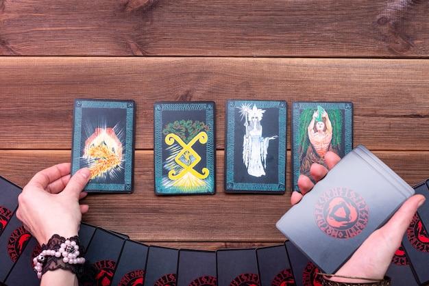 Waarzeggerijkaarten, runenkaarten voor waarzeggerij op een houten tafel. scrying accessoires. uitzicht van boven.