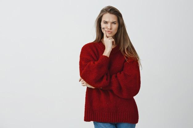 Wacht eens even. perplex humeurige charmante sexy vriendin in rode losse trui pruilt frons gefocust en attent aanraken gezicht, loensen van ongeloof en twijfel met een verdacht gevoel
