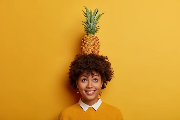 Wacht even, val niet! humoristisch grappig donkerhuidig meisje probeert ananas op haar hoofd te houden, hierboven geconcentreerd