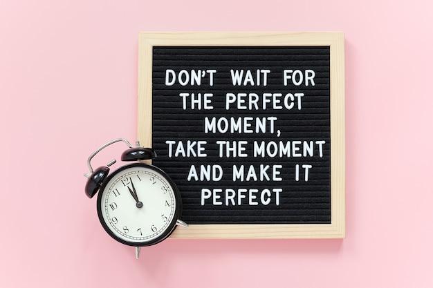 Wacht niet op het perfecte moment, neem het moment en maak het perfect. motiverende citaat op letterbord, zwarte wekker