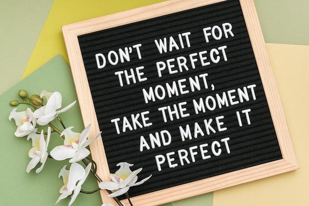 Wacht niet op het perfecte moment, neem het moment en maak het perfect. motiverende citaat op letterbordframe.