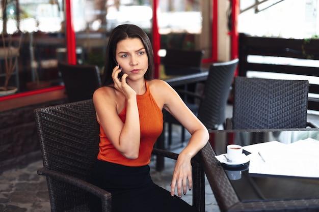 Wacht op een vergadering, wees te laat voor een date. een meisje met een telefoon in haar handen kijkt naar het scherm een trieste kop koffie voor haar, wachtend op haar metgezel of zakenpartner.