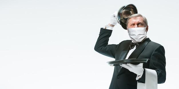 Wacht op je. elegantie senior man ober in beschermend gezichtsmasker op witte achtergrond. vlieger, copyspace. café, restaurantopening. veiligheid tijdens een pandemie van het coronavirus. verzorgen van gasten, klanten.