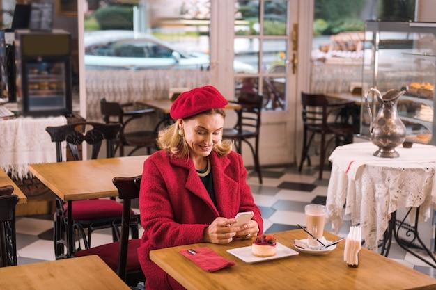 Wachten in café. mooie volwassen elegante dame sms'en haar man terwijl ze op hem wacht in het café