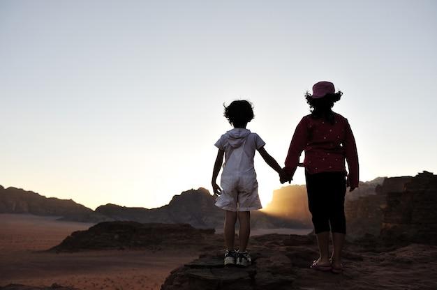 Wachten op de zonsondergang in de woestijn, broer en zus samen op bezoek in afrika. jongen en meisje