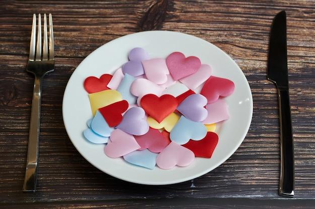 Wachten op een favoriet gerecht in restaurant of café. hart op plaat met mes en vork. liefhebbers ontmoeten elkaar tijdens een dagelijkse lunch.