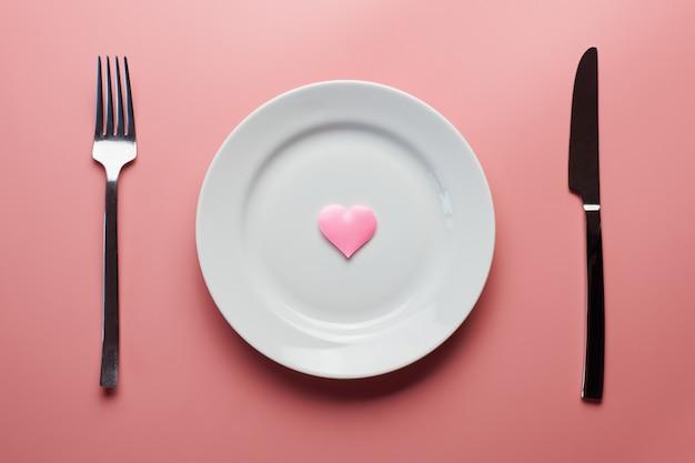 Wachten op een favoriet gerecht in restaurant of café. hart op plaat met vork en mes. liefhebbers ontmoeten elkaar tijdens een dagelijkse lunch.