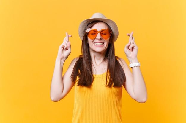 Wachten op een speciaal moment. portret van een glimlachende vrouw in een oranje bril die de vingers gekruist houdt en de ogen gesloten houdt. wens maken. kopieer ruimte geïsoleerd op gele achtergrond. mensen oprecht emoties concept.