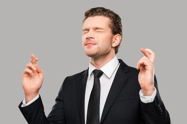 Wachten op een speciaal moment. portret van een jonge man in formele kleding die vingers gekruist en ogen gesloten houdt terwijl hij tegen een grijze achtergrond staat