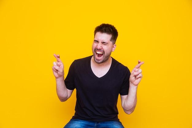 Wachten op een speciaal moment. portret van een jonge man in shirt die vingers gekruist houdt op gele achtergrond.