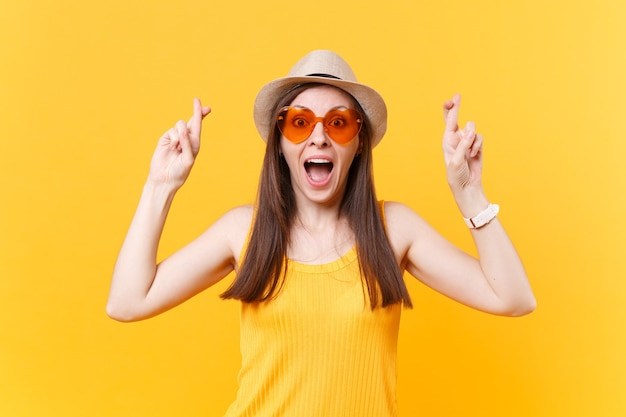 Wachten op een speciaal moment. portret van glimlachende gelukkige vrouw in oranje glazen die vingers gekruist houden. wens maken. kopieer ruimte geïsoleerd op gele achtergrond. mensen oprechte emoties levensstijl concept.