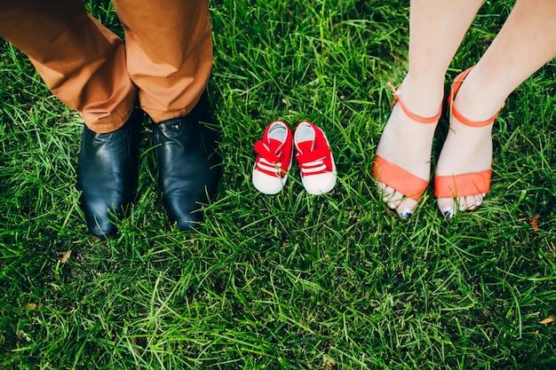 Wachten op een wonder. schoenen voor volwassenen en kinderen. kinderschoenen op het gras tussen de benen van de ouders.