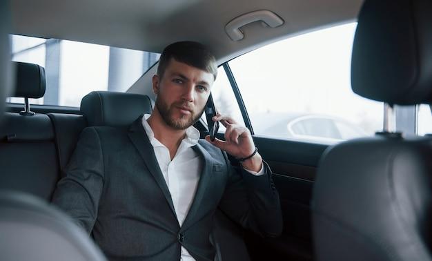 Wachten op het antwoord. zakenman in officiële kleding heeft een telefoontje wanneer hij op de achterkant van de auto zit