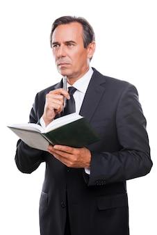 Wachten op inspiratie. doordachte volwassen man in formalwear die een notitieblok vasthoudt en zijn kin aanraakt met een pen terwijl hij tegen een witte achtergrond staat