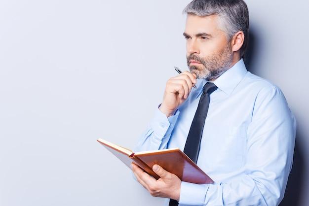 Wachten op inspiratie. doordachte volwassen man in overhemd en stropdas die zijn kin met de hand aanraakt en wegkijkt terwijl hij een notitieblok vasthoudt en tegen een grijze achtergrond staat