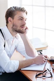 Wachten op inspiratie. knappe jongeman in overhemd en bretels die het hoofd in de hand houden en wegkijken terwijl hij aan tafel zit met boeken erop