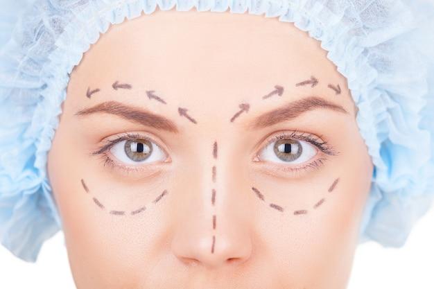 Wachten op plastische chirurgie. bijgesneden afbeelding van mooie jonge vrouw in medische hoofddeksels en schetsen op het gezicht kijkend naar de camera terwijl geïsoleerd op wit