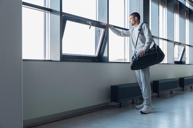 Wachten op poort. sportman loopt naar beneden in modern glazen gebouw, luchthaven in megapolis.