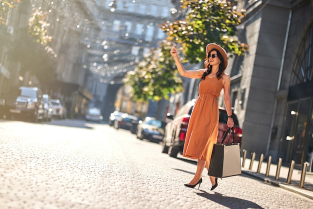 Wachten op taxi. volledige lengte van een jonge, gelukkige modieuze vrouw met boodschappentassen in een lange zomerjurk en schoenen met hoge hakken die buiten op de weg staan. winkelen, mensen levensstijl concept