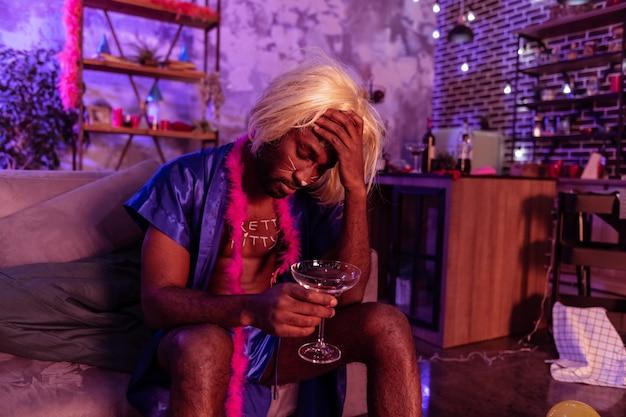 Wachten op voortzetting. moe en dronken man in blonde pruik en vrouwelijke zijden pyjama met kater en bedwelming