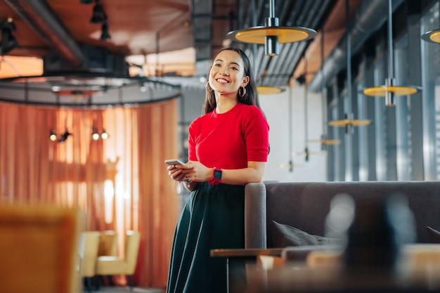 Wachten op vriendje vrolijke donkerharige modieuze vrouw wachten op vriendje in restaurant
