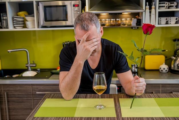 Wachten op zijn vriendin. ongerustente jonge man die enkele roos houdt en in depressie zit terwijl hij in de keuken zit