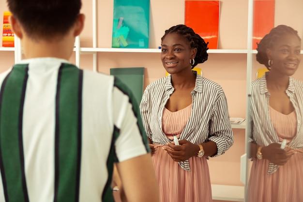 Wachtend op jou. tevreden jonge leraar die een glimlach op haar gezicht houdt terwijl ze met internationale studenten werkt