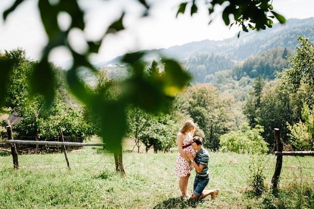 Wachtend schatje. zwangere vrouw met geliefde man staan op het gras. man geknield omhelst en kussende vrouw in een ronde buik. ouderschap. de oprechte tedere momenten. bergen, bossen, natuur
