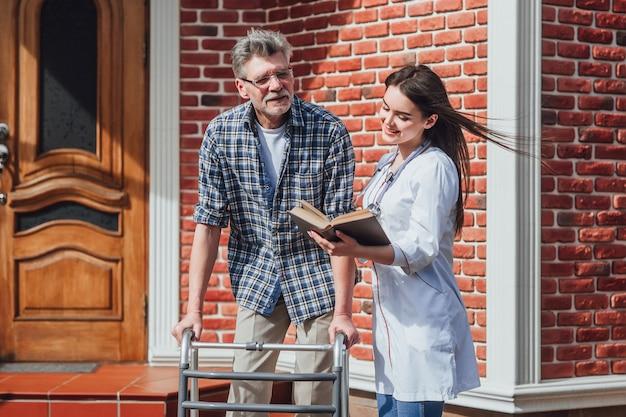 Wachtend wonder verpleegster buitenshuis het verzorgen van een zieke oudere vrouw in rolstoel.