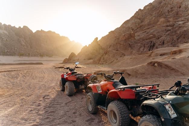 Wachtrij van atv's in de woestijn bij zonsondergang.
