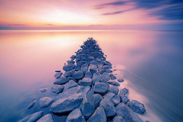 Waddenzee of wadd zee tijdens zonsondergang gezien vanaf steiger met stenen veerboot in de nederlandse provincie friesland