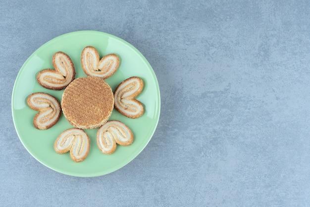 Wafel en koekjes op groene plaat over grijs.