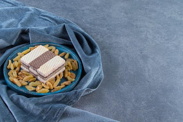 Wafel en rozijnen op een houten plaat op het stuk stof, op de marmeren achtergrond.