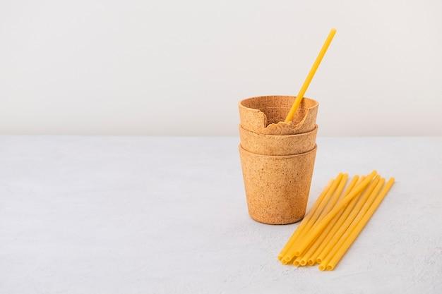 Wafel koffiekopjes en pasta rietjes op neutrale achtergrond met kopieerruimte