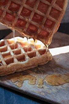 Wafel met honing die op houten tafel valt
