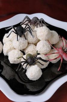 Wafelballen in kokosvlokken in de vorm van spinneneieren op halloween