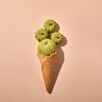 Wafelijsje met groene pompoenen op een crèmekleurige achtergrond.
