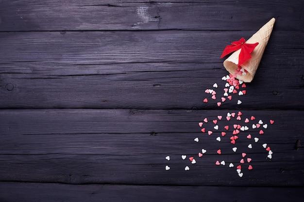 Wafelkegel en veel kleine harten op zwarte achtergrond. verliefdheid achtergrond voor valentijnsdag