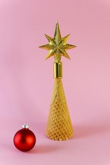 Wafelkegel in de vorm van een kerstboom met een ster op een roze ondergrond.