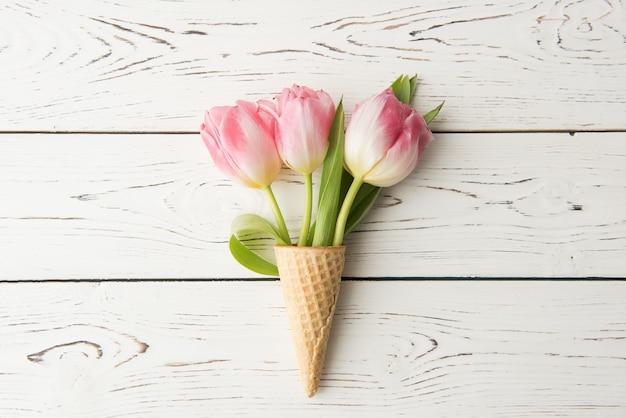 Wafelkegel ligt op een houten vintage tafel. tulpen, lentebloemen