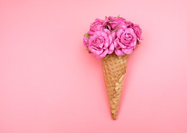 Wafelkegel met bloemen die op roze worden geïsoleerd