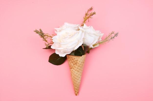 Wafelkegel met bloemen op roze.