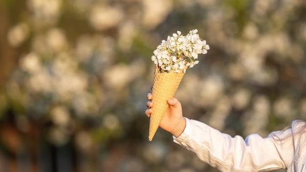Wafelkegel met een boeket van mooie witte kersen bloemen